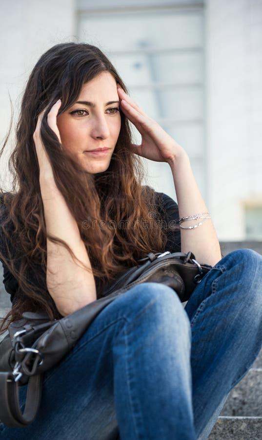 Kopfschmerzen und Probleme - junge Frau im Freien lizenzfreies stockbild