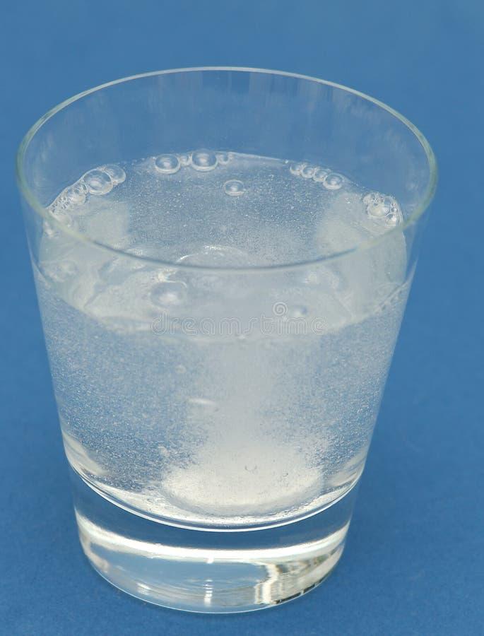 Kopfschmerzentabletteluftblasen im Wasser lizenzfreie stockfotos