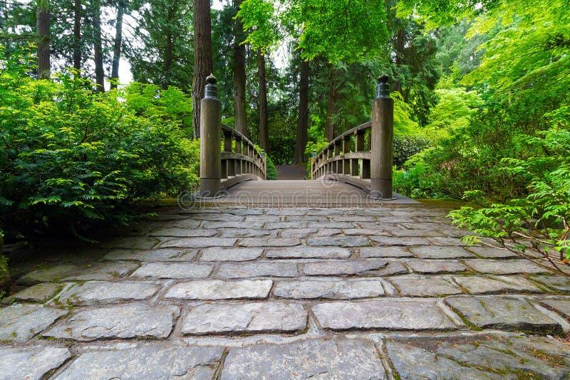 Kopfstein-Weg zur hölzernen Brücke in manikürtem japanischem Garten stockfoto