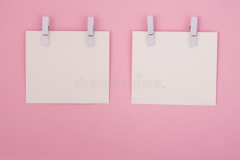 Kopieerruimte Twee witte stukjes papieren ivoor met clothespins op een lichtroze royalty-vrije stock foto's