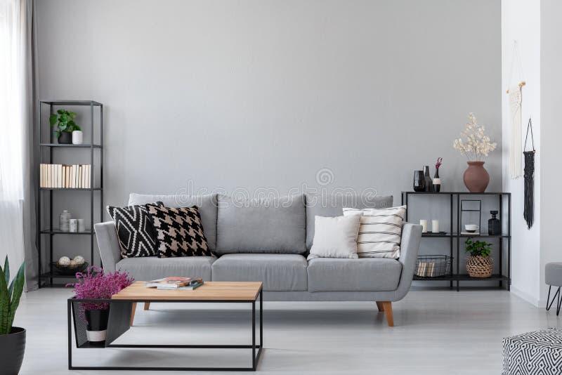 Kopienraum auf der Wand des skandinavischen Wohnzimmers mit moderner Couch, Metallregalen und industriellem Couchtisch stockbilder