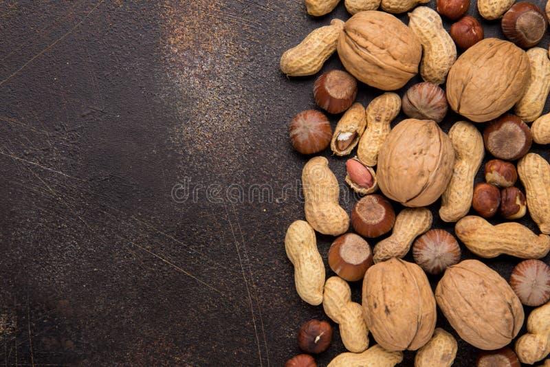 Kopienraum mit Nüssen in einem Oberteil Walnüsse, Haselnüsse und Erdnüsse auf dunklem Hintergrund Geschmackvoller gesunder Imbiss lizenzfreie stockfotos
