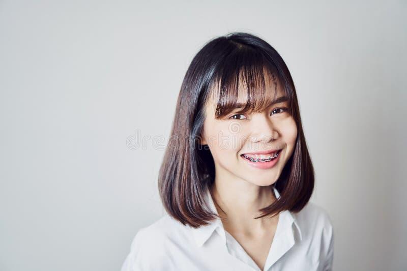 Kopienraumporträt der lächelnden asiatischen jungen Frau setzte an die Klammern stockfotografie