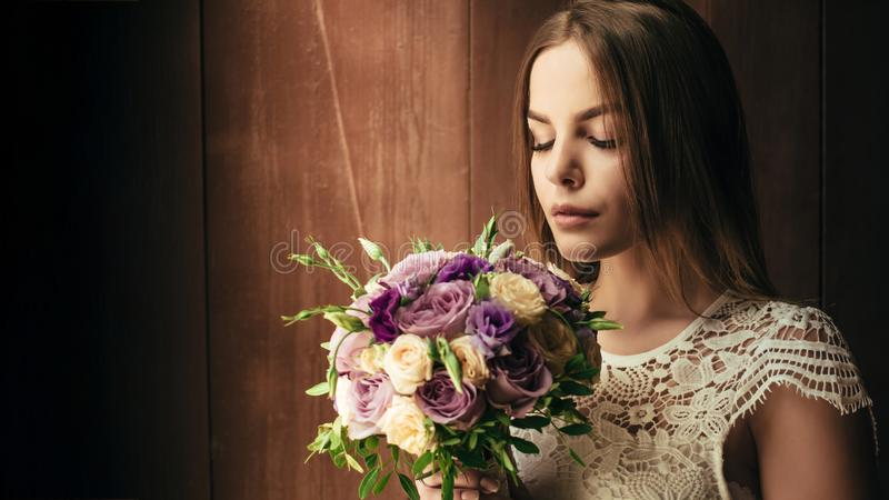 Kopiera utrymme, din text här, flickainnehavblommor i händer, ung härlig brud i den hållande bröllopbuketten för den vita klännin royaltyfri bild