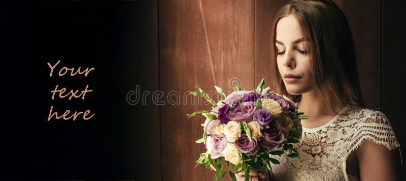 Kopiera utrymme, din text här, flickainnehavblommor i händer, ung härlig brud i den hållande bröllopbuketten för den vita klännin arkivbilder