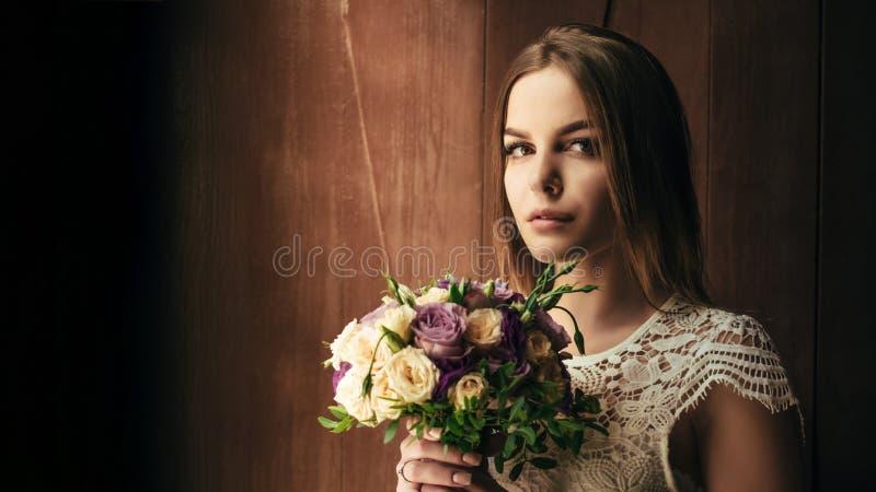 Kopiera utrymme, din text här, flickainnehavblommor i händer, ung härlig brud i den hållande bröllopbuketten för den vita klännin arkivfoto