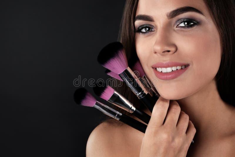 kopierar härliga borstar för bakgrund den mörka kvinnan för makeupståendeavstånd arkivfoton