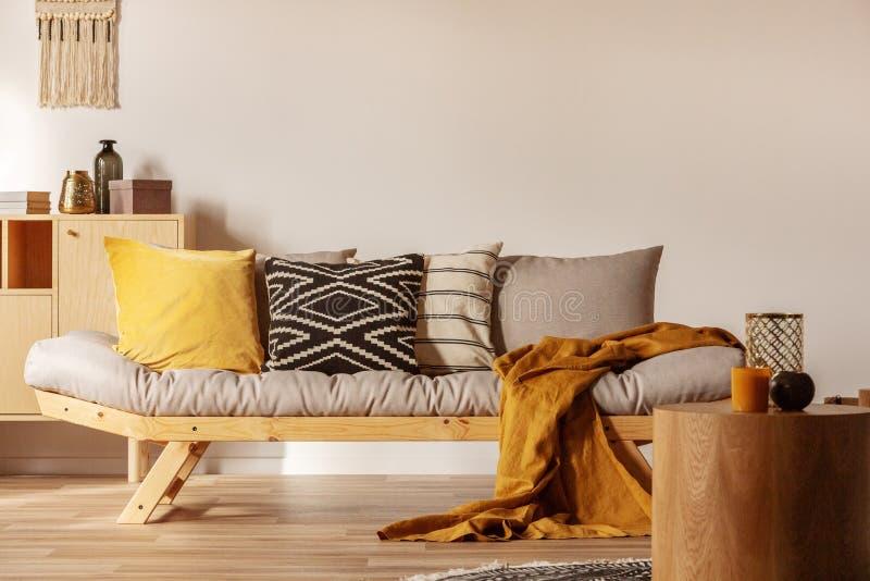 Kopieren Sie Platz auf leere, weiße Wand des modernen Wohnzimmerinneren mit gelb- und orangefarbenen Akzenten. stockfotografie