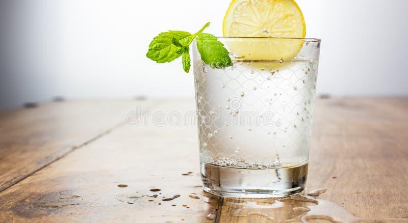 Kopieringsspaсe - exponeringsglas av kolsyrat vatten på en tabell med en citron och en mintkaramell arkivfoto