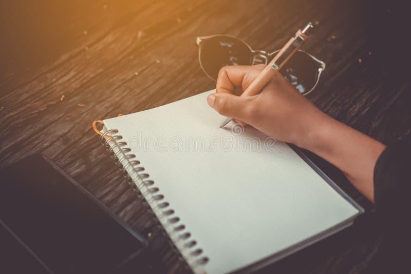 Kopieringsutrymme av kvinnahanden som ner skriver i den vita anteckningsboken med solljus royaltyfria foton