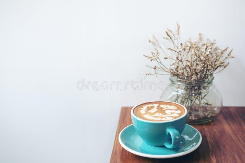 Kopieringsutrymmebilden av en blå kopp av varmt lattekaffe och torkar blommor i en vas på tappningträtabellen arkivbilder