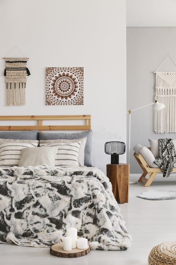 Kopierte Blätter auf Bett nahe bei Lampe auf hölzernem Schemel im Schlafzimmerinnenraum mit Plakat stockfoto