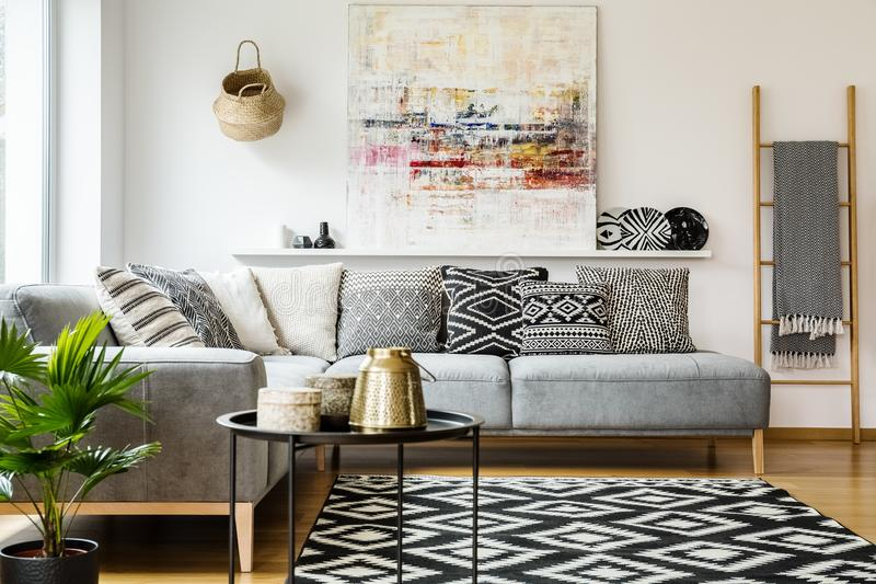 Kopierte Kissen auf grauem Ecksofa in Wohnzimmer Innenwi lizenzfreie stockfotos