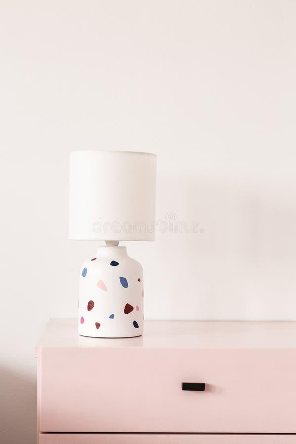 Kopierte Lampe auf Pastellrosakabinett gegen weiße Wand im colo lizenzfreie stockbilder
