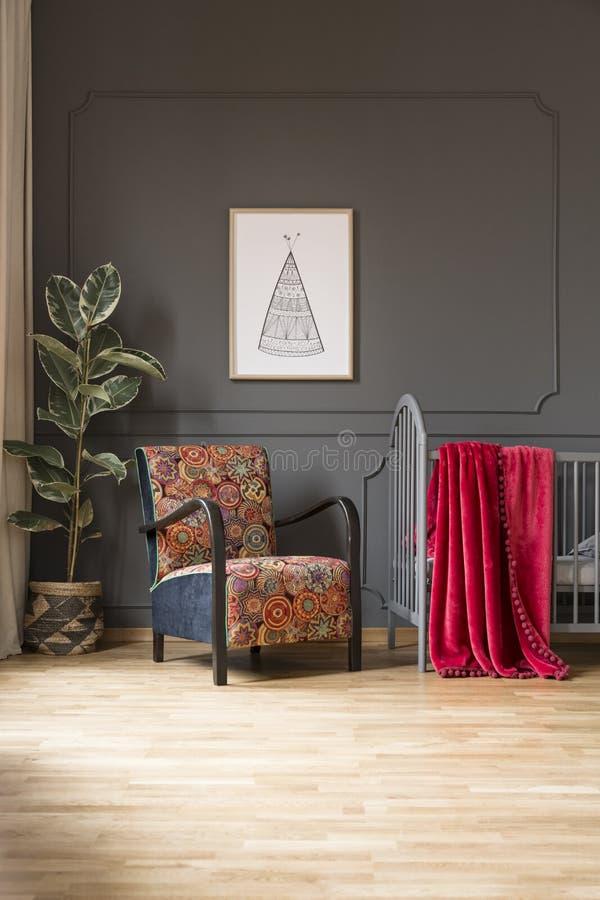 Kopierter Lehnsessel nahe bei Bett mit roter Decke in Baby ` s bedroo lizenzfreie stockbilder