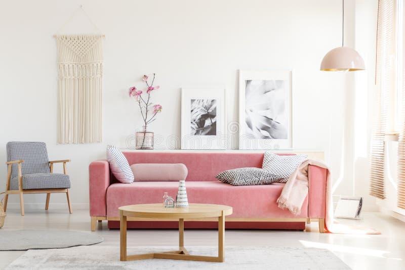 Kopierter Lehnsessel und rosa Couch im feministischen Wohnungsinnenraum stockfoto