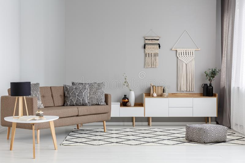 Kopierter Puff auf Teppich nahe braunem Sofa in modernem Wohnzimmer I lizenzfreie stockfotos