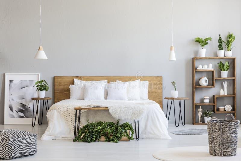 Kopierter Puff und Korb im hellen Schlafzimmerinnenraum mit Lampen, lizenzfreie stockfotos