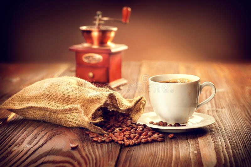Kopp av aromatiskt kaffe på tefatet med säcken som är full av grillad coffe royaltyfri foto