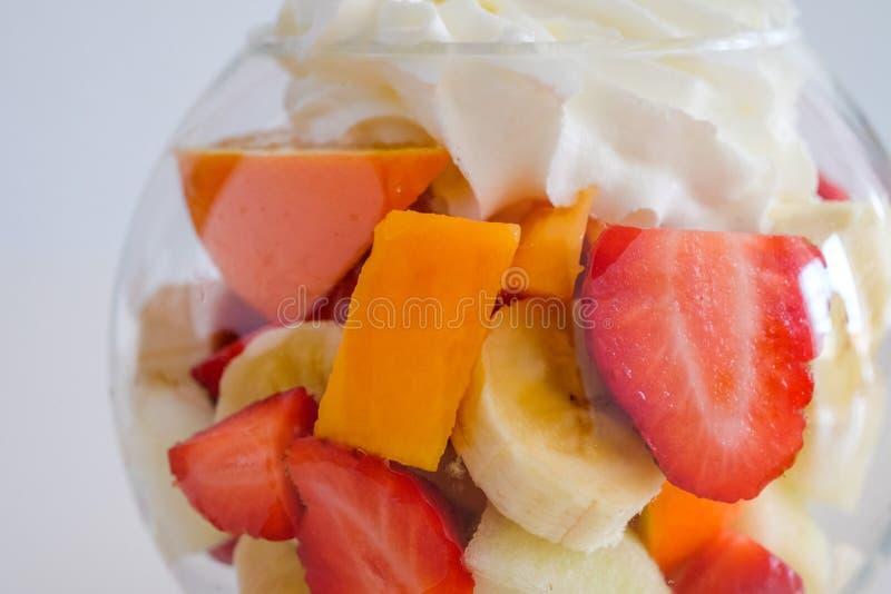 Kopp av blandade frukter med kräm upp royaltyfria foton