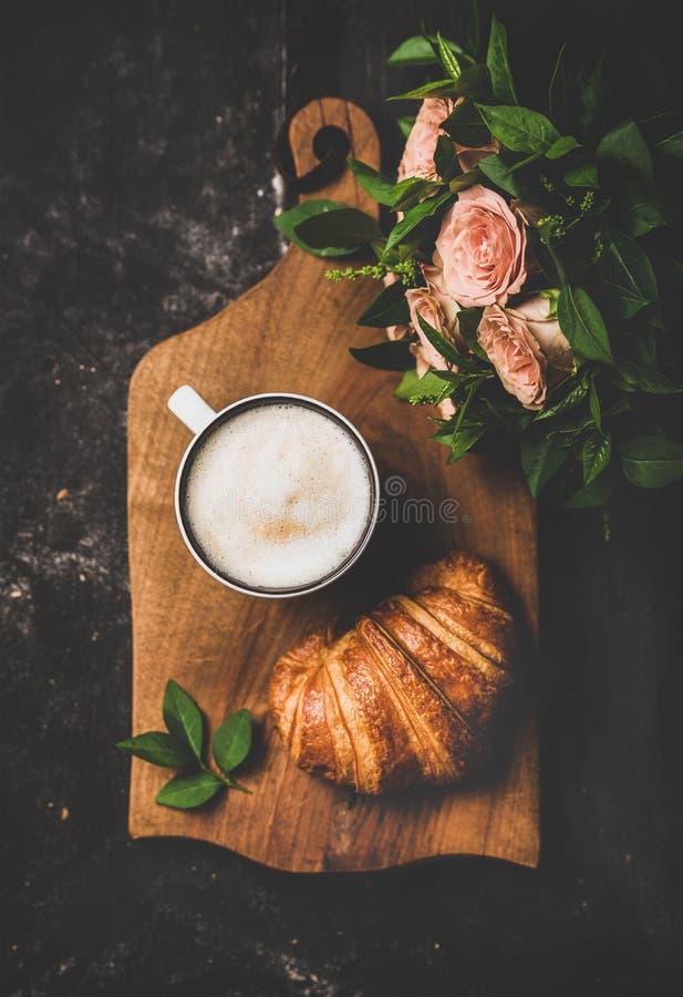 Kopp av cappuccino, gifflet och buketten av rosa blommor royaltyfri fotografi