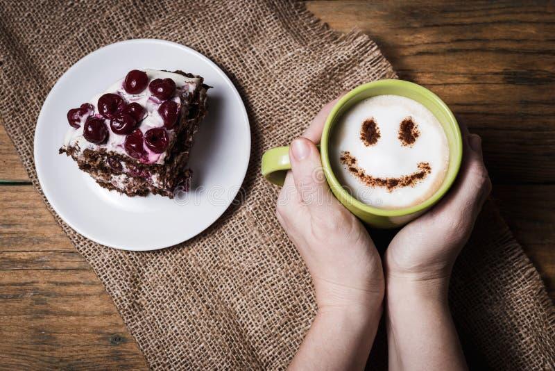 Kopp av cappuccino med leende och den körsbärsröda kakan royaltyfria foton