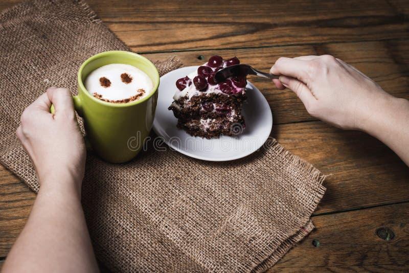 Kopp av cappuccino med leende och den körsbärsröda kakan arkivfoton