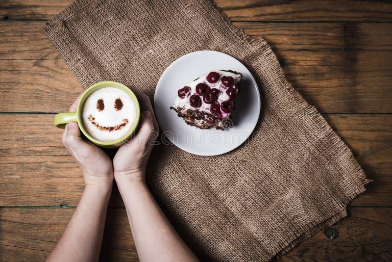 Kopp av cappuccino med leende och den körsbärsröda kakan fotografering för bildbyråer