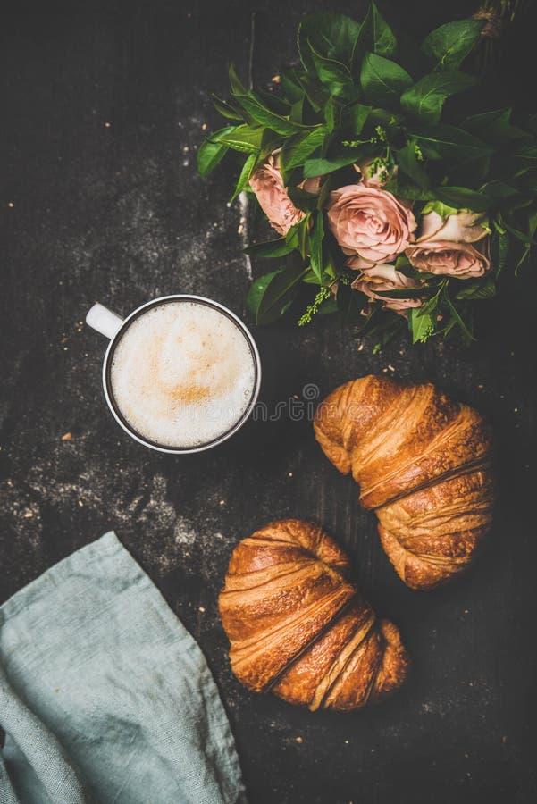 Kopp av cappuccino, nya giffel och blommor över sjaskig bakgrund royaltyfri foto