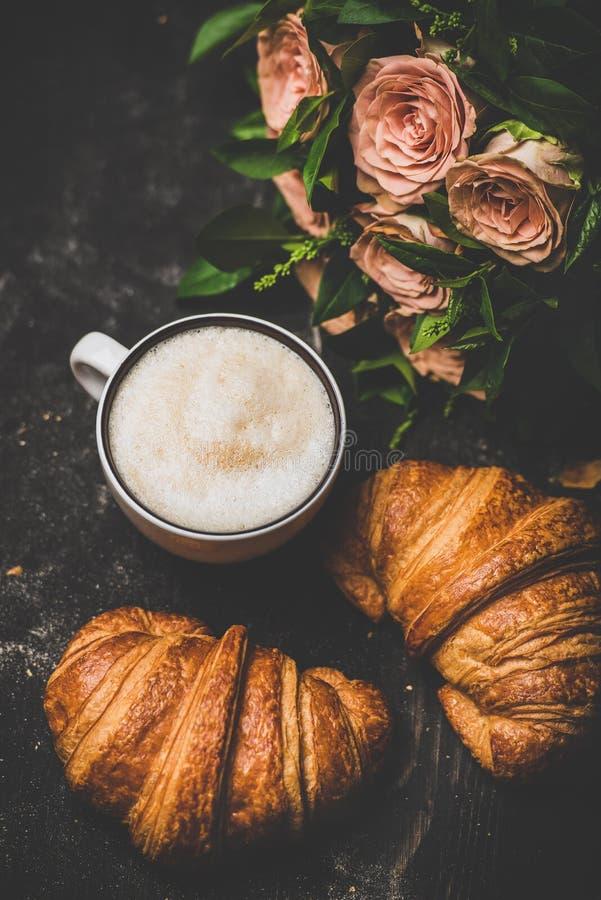 Kopp av cappuccino, nya giffel och buketten av rosa blommor royaltyfria foton