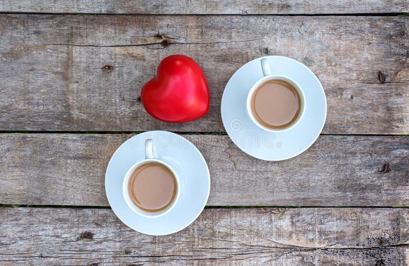 Kopp av cappuccino- och hjärtaform i trätabellen fotografering för bildbyråer