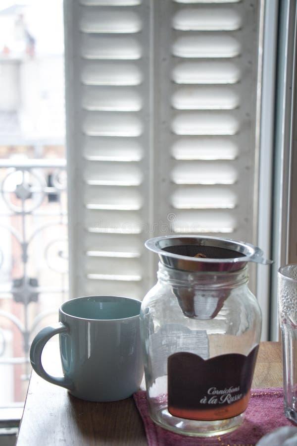 Kopp av den varma kaffe- och exponeringsglaskruset mot fönster med metallslutare arkivfoto