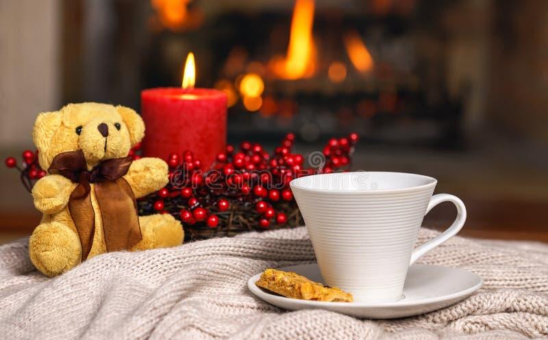 Kopp av den varma stearinljuset för drinknallebjörn i röd julgarnering på den hemtrevliga stack plädet framme av den varma spisen royaltyfri bild