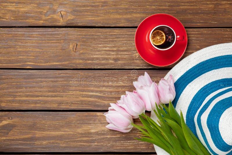 Kopp av engelskt te med den vårtulpan och hatten fotografering för bildbyråer