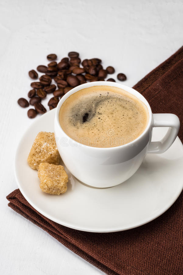 Kopp av espresso med rottingsocker och bönor arkivfoto