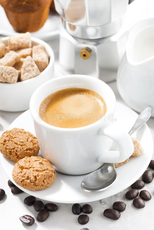 Kopp av espresso och kakor på en vit tabell som är vertikal royaltyfri fotografi