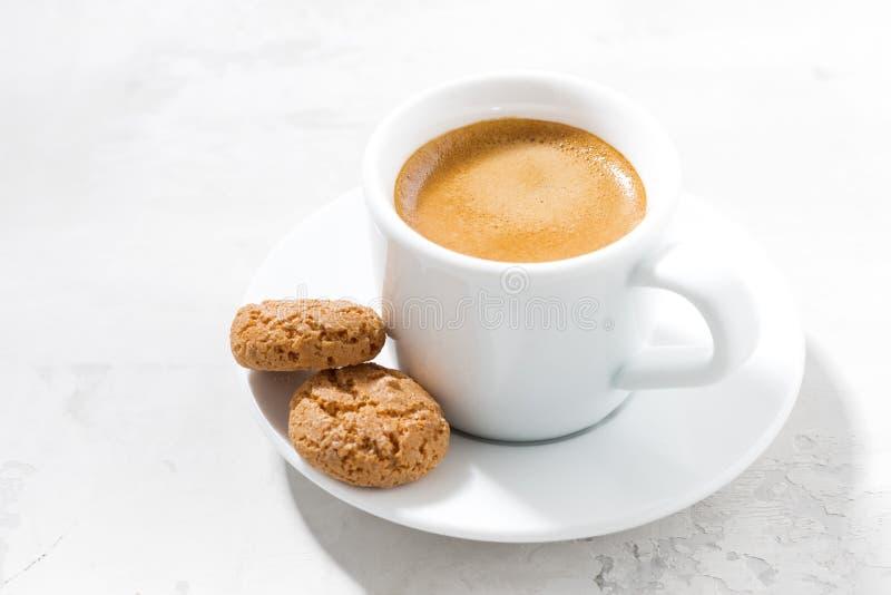 Kopp av espresso- och mandelkakor på en vit tabell arkivfoton