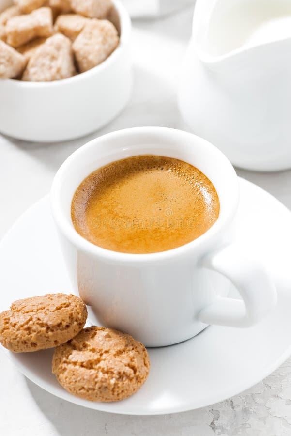 Kopp av espresso- och mandelkakor på en vit tabell, closeup royaltyfria bilder
