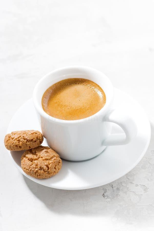 Kopp av espresso- och mandelkakor på en vit tabell, lodlinje royaltyfri foto
