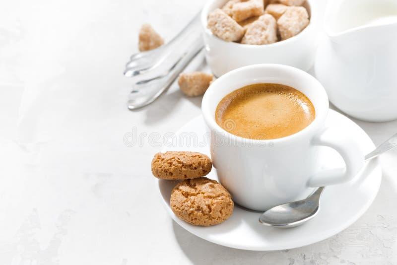 Kopp av espresso- och mandelkakor på en vit tabell som är horisontal royaltyfri foto