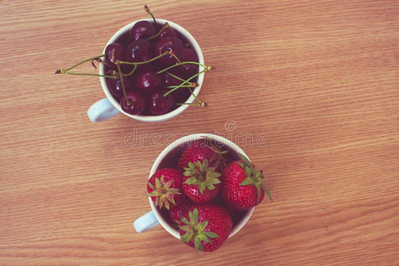 Kopp av körsbär och jordgubbar arkivbild