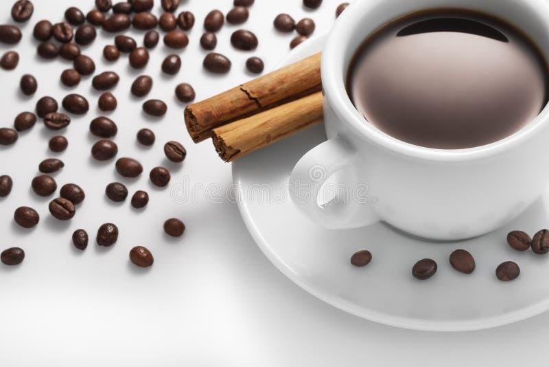 Kopp av kaffe med kanel och bönor arkivbild
