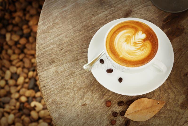 Kopp av konstlattekaffe med tappningsignal arkivfoton