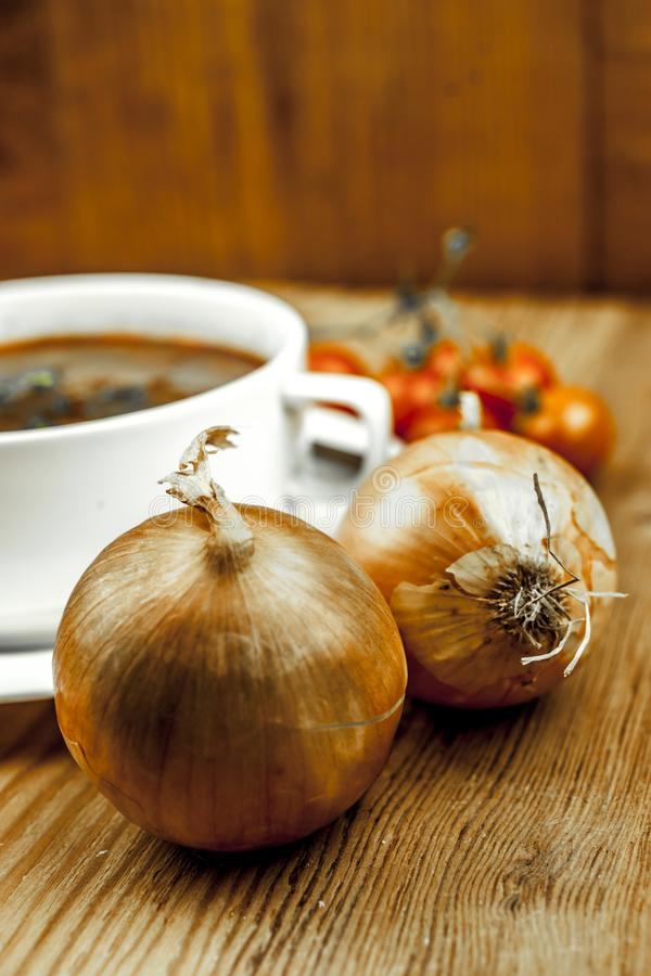 Kopp av löksoppa med två lökar royaltyfria foton