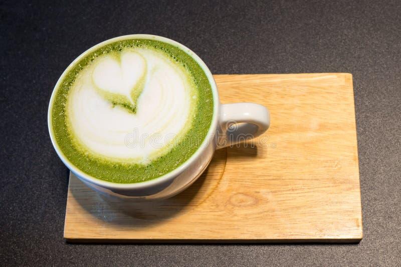 Kopp av lattekonstkaffe på trä royaltyfri foto