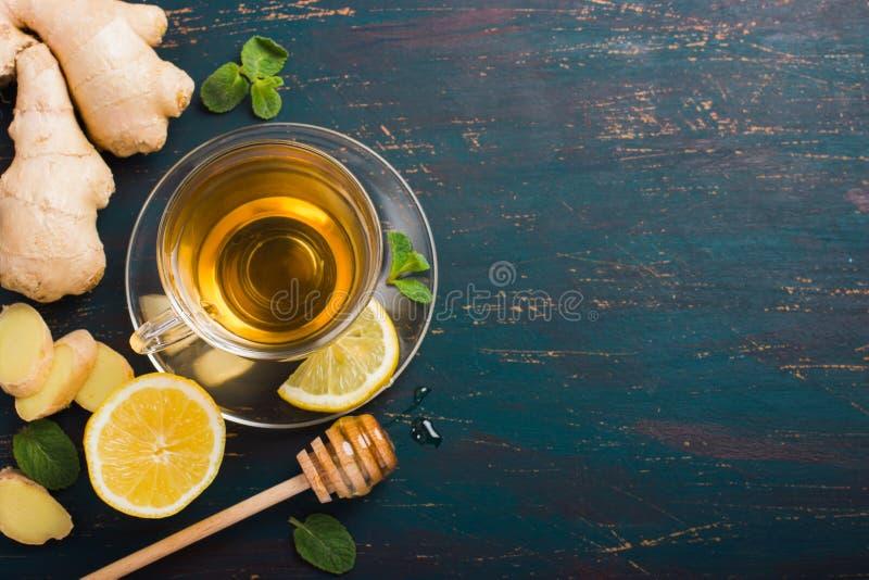 Kopp av ljust rödbrun te med citronen och honung royaltyfri bild