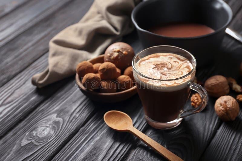 Kopp av smaklig varm choklad med godisar och muttrar på den mörka trätabellen royaltyfri fotografi