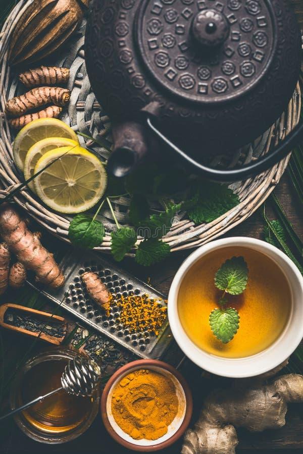 Kopp av sunt gurkmejakryddate med järntekannan och ingredienser: citron, ingefära, kanelbruna pinnar och honung, bästa sikt royaltyfria foton