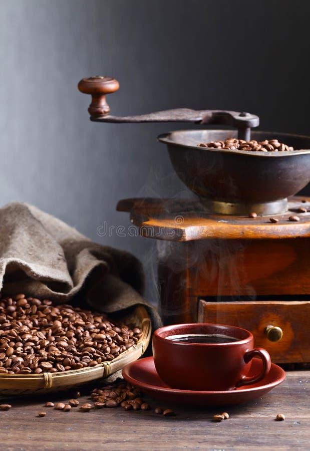Kopp av svart kaffe, kaffekvarn och grillade bönor royaltyfri foto