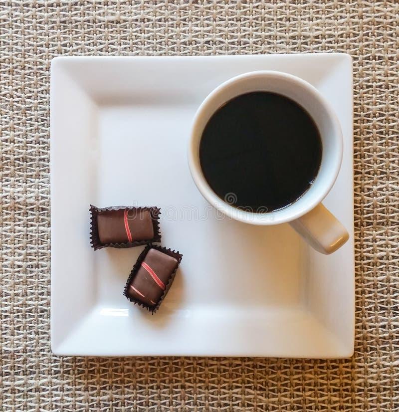 Kopp av svart kaffe med godisen arkivbilder